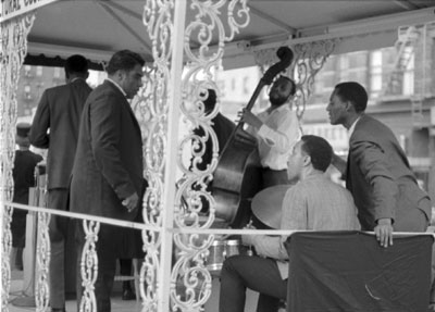 From left: John Gilmore (with back to camera), unknown, Don Moore on bass, Billy Higgins on drums, unknown on right.